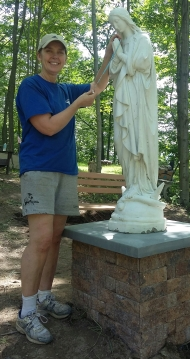Placing a Rosary in the hands of Our Lady.